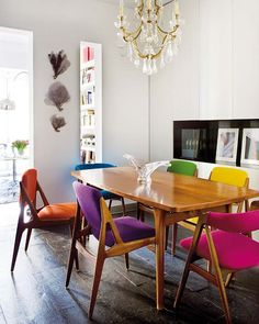 Table and chairs from the Mid-century design school take on bright colours . . . pretty chandelier and ever contemporary white walls make for an eclectic scheme.
