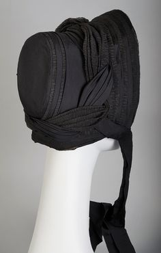 """Mourning bonnet of black silk crepe and taffeta, American, ca. 1860, KSUM 1995.17.447.  This mourning bonnet is one of the four pieces from Kent State included in """"Death Becomes Her"""" which runs through February 1, 2015 at the Met's Costume Institute."""