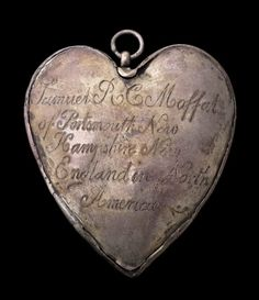 "This amulet consists of two heart-shaped plaques, both slightly convex, joined with a narrow strip of silver. The engraved, cursive inscription on the back reads: ""Samuel R C Moffat / of Portsmouth New / Hampshire New / England in North / America."" Engraved on the front is a cartouche with a shield-shaped heraldic device with several bird images. Charms of this type were made to enclose the caul of the owner and were considered protection against drowning."