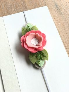 This Felt Flower Bookmark is perfect for anyone that loves to read or journal. The thin elastic slides around the front cover and the page you are reading or writing on, keeping your place. The universal size fits most hard or soft cover books and journals. Soft muted tones of wool felt