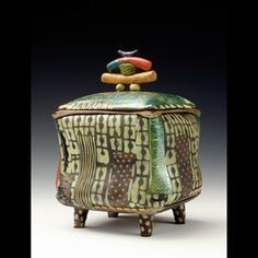 """Daniel Oliver Ceramics, Urn Series - """"I hand build my work. It gives me freedom to create my pieces. I begin with a slab or extruded piece of clay, add textures on the surface then shape my forms until I am pleased with what I see. I mostly do Raku firing which gives my work an earthy look. I brush, stamp or trail glaze my designs. I started the urn series after a returning customer asked me to make him a box for his mother's ashes. The box had to be the size or holding capacity of a shoe…"""