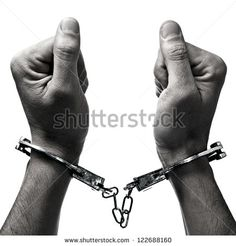 closeup of the hands of a man with handcuffs on a white background - stock photo