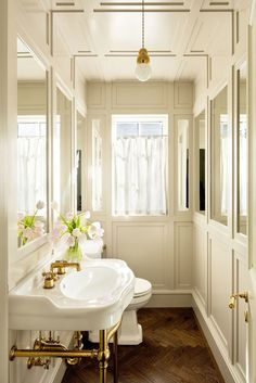 The powder room is narrow, but it feels more spacious because of the rows of mirrors placed on each opposing wall. A single, stunning light by Studio Michael Anastassiades hovers over the space.   A 1920s House with a Modern Twist in Portland, Oregon Photos   Interior designer Jessica Helgerson   Architectural Digest
