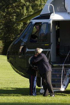 George W Bush U.S. President George W. Bush hugs a Marine guarding his helicopter after stepping off Marine One after returning to the White...