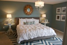 Love this master bedroom. That is the chandy I want and I already have a similar color paint for the walls. Love the graphic punch of the rug and the white frames & mats for the photos. Ikea?