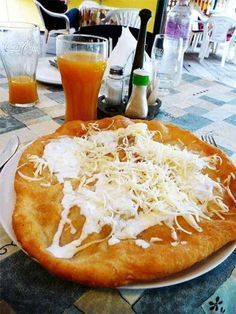laan-gosh) a simle, tasty and filling Hungarian fast food. Similar to American Indian Fry-bread, but this potato dough is a bit different. Traditionally you rub a clove of garlic over the hot top and then add cheese and sour cream. Hungarian Cuisine, Hungarian Recipes, Dumplings, Budapest, Hungary Food, Great Recipes, Favorite Recipes, Good Food, Yummy Food
