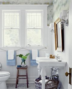 Adorable bathroom: rope towel rack, wainscoting, map wallpaper, small octagon white tile floor...