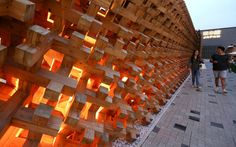 Visitors pass the outside of the Japan pavilion at the Expo 2015 exhibition in Milan, Italy.
