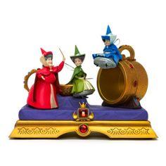 """Heiße die drei Feen aus """"Dornröschen"""" in deinem Palast willkommen! Diese wunderschöne """"Disneyland Paris""""-Figur zeigt Flora, Fauna und Sonnenschein mit einer goldenen Tasse und einem goldenen Löffel."""