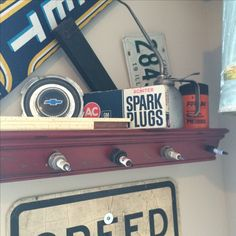 Shelf I made with old spark plugs instead of pegs.    Vintage Car and truck Decor decorations Man Cave Boys Room Garage Look Shop Look DIY Tools License Plates etc.