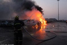 Blazing: A firefighter tries to extinguish the flames as fire ravages through a fleet of more than 1,000 cars near the warehouse explosion