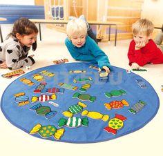 Candy XXL  Dit kleurrijke spel bevorderd het waarnemingsvermogen en het herkennen van kleurencombinaties. 41 snoepjes liggen door elkaar op het kleed. De spelers gooien met 3 kleurendobbelstenen, vervolgens moet het snoepje met de juiste kleurencombinatie gevonden worden. Er zijn 3 verschillende mogelijkheden om het spel te spelen én het spel te winnen. Nu in extra grote uitvoering voor een extra dimensie in het spelplezier.   Geschikt vanaf: 4 jaar