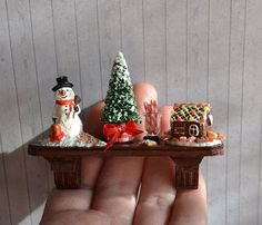 Dollhouse miniature Christmas scene with snowman, tree, and gingerbread house