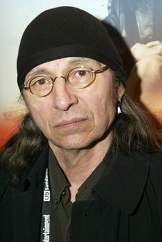 """John Trudell, Actor: On Deadly Ground. John Trudell was born in Omaha, Nebraska, to a Santee Sioux father and Mexican Indian mother. After a stint in the Navy (and Vietnam) from 1963 to 1969, he became involved with the American Indian Movement, becoming National Chairman in 1973. He held that position until 1979; it was then that his wife Tina, mother-in-law, and three children ages one, three, & five, were burned to death in a """"fire..."""