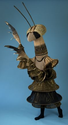 Praying mantis costume with  basketry woven head piece and arms In natural  color reed with black and gold hoop dress