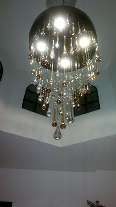 Candil de vidrio soplado en color ambar y natural, artesanal de Tonalá, Jal. Colgando de una cúpula.