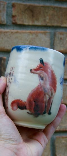 Made by Lone Fox Pottery Wine Cup, Hand Painted Red Fox Sitting, Handmade, Hand thrown, Pottery, Ceramic, Stoneware, Tumbler. Standard size wine cup with matte finish, glossy blue interior, and a red fox sitting design. The design is hand painted, therefore each cup will be sightly different and unique. Created by drawing out the fox on the cup and then painting over the sketch. Finished with a warm matte glaze.Holds 10oz