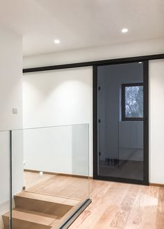 Glazen schuifdeur met zwart geanodiseerd aluminium van ANYWAYdoors met grijs in de kern gekleurd glas.