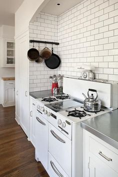 Fabulous Wedgewood Stove filling kitchen alcove framed by white cabinets with nickel hardware and zinc countertops below a subway tiled alcove highlighted by gray grout.