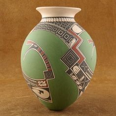 This Mata Ortiz Pottery features a hand polished, multicolored design on a hand coiled, hand built wall of clay. Made by Master Potter, Victor Reyes, this piece is exquisite in its combination of warm reds & browns against a vibrant green background. Singular geometric symbols swirl across this egg-shaped pot that are derived from the ancient 'Paquime' style. $440.00 #Alltribes