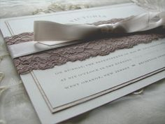 The soft colours, lace, and bow on this invitation will melt anyone's heart. This romantic, vintage invitation features ecru linen cardstock, a middle layer that's a dusty rose colour in some angles but shimmers with touches of gold at other angles, and metallic dusty rose envelopes. The fonts are a sturdy block with a modern calligraphy script, all topped with a monogramed laurel. Find the details at http://www.teajamandwed.com/#!victoria--shane--rustic/c12p2