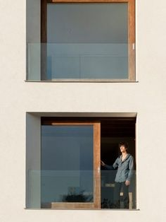 The white plaster facade contrasts the natural wooden window frames.