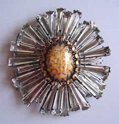 SCHREINER  unsigned ruffle  		brooch with long unfoiled clear rhinestone edges and a center with of an caramel  		art glass cabochon surrounded by reverse mounted rhinestones, hook for pendant  	on the back, circa 1960, 3-1/8.