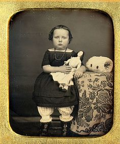 "Very early antique photo of little girl with her doll. There appears to be a ""muff"" sitting on the table besider her. With her petticoat showing and the severe hairstyle, I'd guess circa 1870, possibly a little earlier."