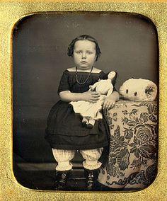 """Foto antigua muy temprano de la niña con su muñeca. Hay ppears ser un """"manguito"""" sentado en la mesa de su besider. Con su actuación enagua y el peinado severo, supongo alrededor de 1870, posiblemente un poco antes."""