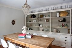 A pale blue-gray on the walls and a darker warm gray behind the open shelving help give this modern farmhouse dining room its eclectic vibe.