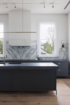 The kitchen features basalt countertops and metal cabinets with pulls from Bäccman & Berglund in Sweden. Above the island hangs a single, linear Highline pendant from Australian architecture firm Archier.