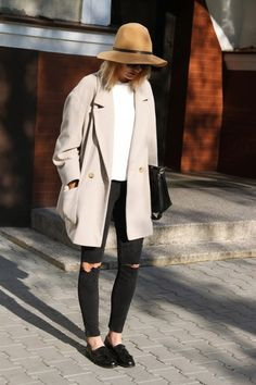 oversized coat with white tee and black, ripped jeans. a khaki-colored hat, black purse and black loafers finish off the look.