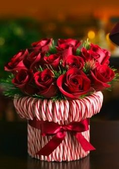 Stretch a rubber band around a cylindrical vase, then stick in candy canes until you cant see the vase. Tie a silky red ribbon to hide the rubber band. Fill with red and white roses or carnations. Good hostess gift for holiday parties.
