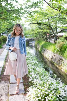 Jessica Sturdy on Philosopher s Path in Kyoto Japan wearing a denim jacket and pleated pink midi skirt Spring Outfits Japan, Japan Outfits, Japan Spring Fashion, Japan Summer Outfit, Pink Skirt Outfits, Pink Pleated Skirt, Pink Skirts, Look Rock, Jupe Midi Rose