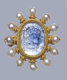 DescriptionGold brooch with a central sapphire cameo head of Medusa in a heavy ropework setting bordered with pearls, each pinned to a stem decorated with ropework. The pins are stopped at the outer edge with minute cabochon rubies. The setting is marked on the reverse with the maker's mark in applied wirework and an engraved monogram on the back of the cameo.. More  Producer nameWorkshop of: Castellani biography Date1870 (circa)