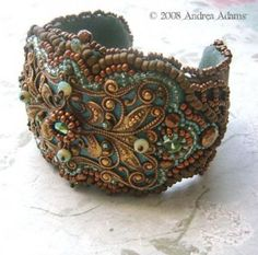 Bead embroidered cuff bracelet worked around a large vintage brass filigree. Embellished with vintage facetted glass cabochons and beads, as well as seed beads in shades of mossy green, old brass and bronze. Measures about 5 & 1/2″ wide by 2″ high and will flex to fit most wrists. It is backed with soft ultrasuede for maximum comfort.