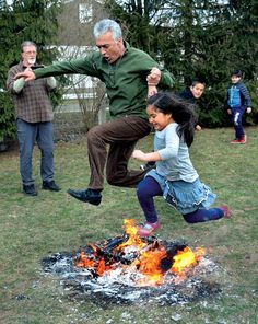 Ibrahim Parlak and Vivi Van Plew-Cid leap over the traditional Newroz fire at Cafe Gulistan in Harbert on Sunday, March 25. - photo by David Johnson