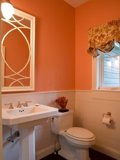 Too many decorations can make a small space even smaller. A pretty curtain and coral-colored wall are all this little bathroom needs to make a big impression.