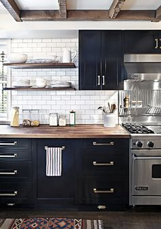 dark kitchen cabinets, white subway tile, wood countertop, stainless steel, open shelving, brass