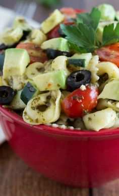 pasta, avocado, olives, cucumber and tomatoes with italian dressing and pesto