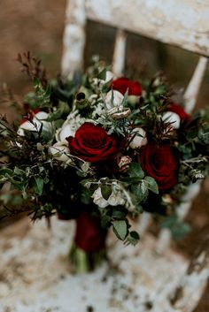 Moody winter woodland wedding bouquet with red roses, blue thistle, gumnuts and foliage | Woodlands Creative Photography and Film