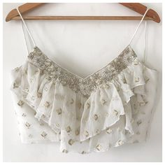 A dreamy blouse with 2 layers of ruffles can be paired with literally anything. Blouse is in georgette with thread and zari embroidery all over, and a carefully hand embroidered neck line using pearls, dabka, Cut daala, poth, zari etc. This blouse is ideal for a boho destination wedding! Blouse has a side zip and com