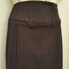 """Navy and White Pinstripe Pencil Skirt NWOT Classic navy and white pinstripe pencil skirt gets updated. Featuring a high shaped waistband with tab details see photo 4. The back of the skirt features gold self-belt hardware on back see photo 3. This skirt is fully lined has a side invisible zipper closure and slit at the back hem to allow great fit and easy movement. Very fitted silhouette.  61% poly 34% rayon 5% spandex 95% poly, 5% spandex lining  Machine washable  30"""" waist 38"""" hips 38""""…"""