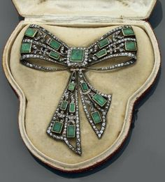 Emerald devant de corsage. in the shape of ribbon bow, set with rectangular emeralds, rose cut diamonds, mounted pink gold and silver, Portugal or Spain, the first half of the 18th century, gross weight: 40.5 gr, dimensions: 8.2 x 9 cm, witha original case