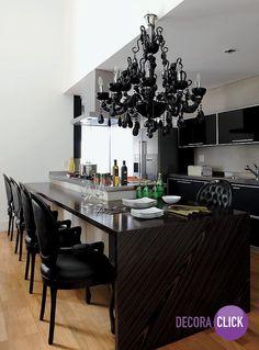 O preto é sempre imponente! Nesta sala de jantar integrada com a cozinha ficou ousado. O lustre de candelabro trouxe um toque de sofisticação.