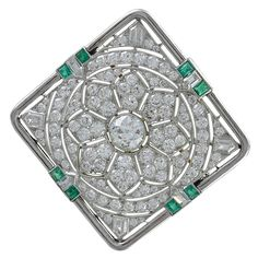 Gorgeous Art Deco Diamond Emerald Gold Platinum Pin. Superb, beautiful antique diamond and emerald brooch. Approximately 8.0 carats of round brilliant diamonds, F color, VS2 clarity. Center stone is a1.0 ct, full cut diamond. Surrounded by many round brilliant and some tapered baguette diamonds in a very finely pierced, mesmerizing pattern. It glows softly and almost looks like it is moving in the light. Accented with eight emerald cut emeralds. Set in platinum