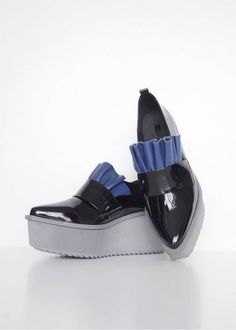 Step out in these sleek, and edgy loafer style shoes with platform heel. Beautifully crafted from 100% leather, features bright blue ruffle detail across the front for a feminine touch. The grey colored platforms provide extra comfort and are perfect for wearing all day. Style with oversize and menswear pieces. Made from patent black leather, a sexy update of the best seller from Jamie Wei Huang.