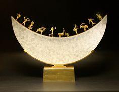 "*Art Glass - ""Glass Moon Sculpture"" by Georgia Pozycinski and Joseph Pozycinski  (A series of wax cast figures adorns the top edge of a kiln-cast glass crescent moon sculpture that sits atop a bronze base.)"