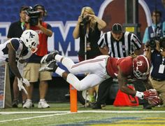 Alabama running back Derrick Henry (27) dives into the end zone for a touchdown as West Virginia safety Dravon Henry (6) defends during the second half of an NCAA college football game Saturday, Aug. 30, 2014, in Atlanta. (AP Photo/John Bazemore)