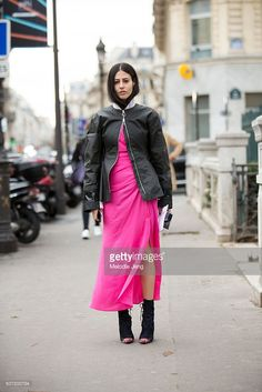 Gilda Ambrosio of Grazia Italy wears a a black Dior bomber jacket zipped at the neck and a Alessandra Rich slit pink dress at the Jean Paul Gaultier show on January 27, 2016 in Paris, France.
